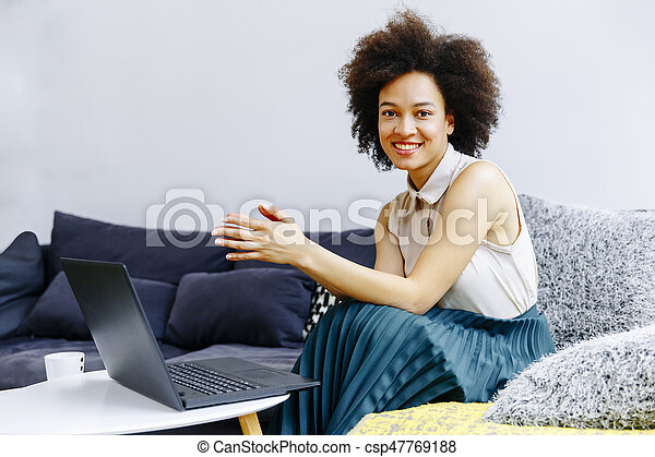 Young woman with curly hair, uses laptop and sitting on the sofa at home - csp47769188