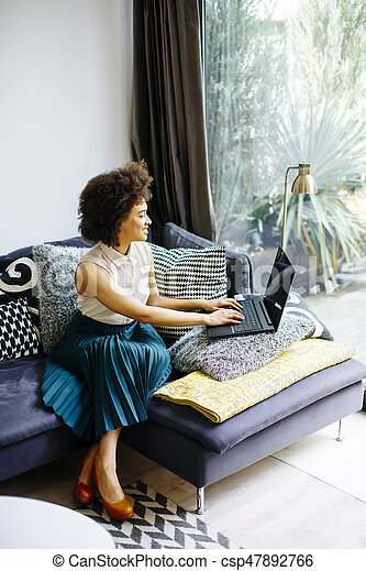 Young woman with curly hair, uses laptop and sitting on the sofa at home - csp47892766