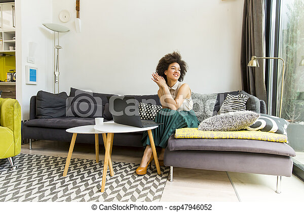 Young woman with curly hair, uses laptop and sitting on the sofa at home - csp47946052