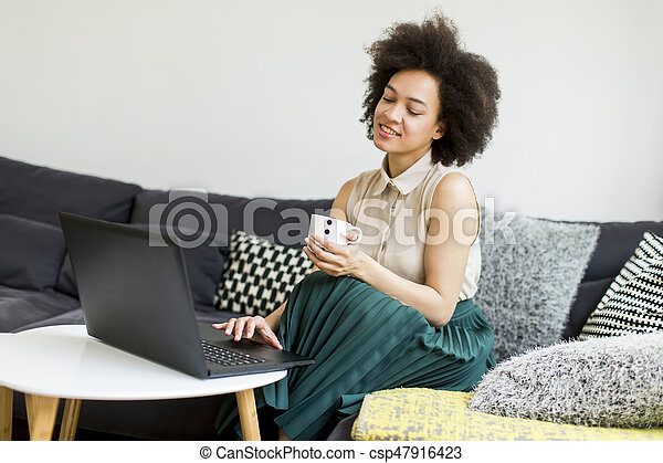 Young woman with curly hair, uses laptop and sitting on the sofa at home - csp47916423