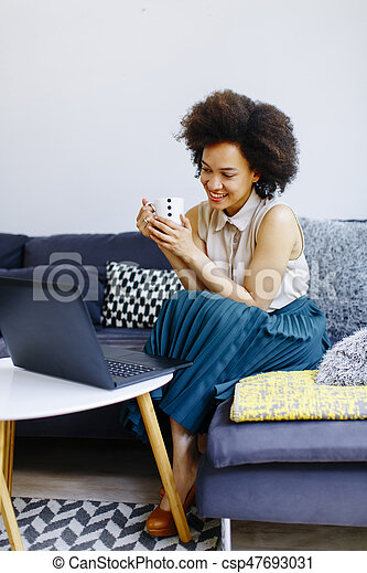 Young woman with curly hair, uses laptop and sitting on the sofa at home - csp47693031