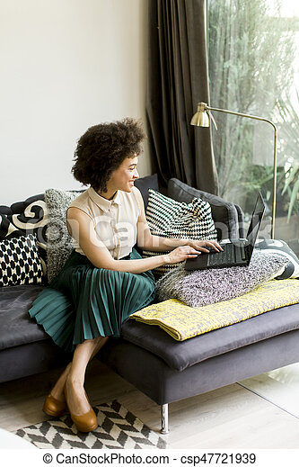 Young woman with curly hair, uses laptop and sitting on the sofa at home - csp47721939
