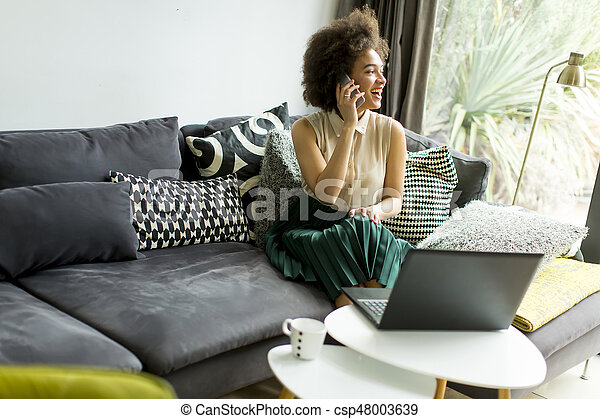 Young woman with curly hair, uses laptop and sitting on the sofa at home - csp48003639