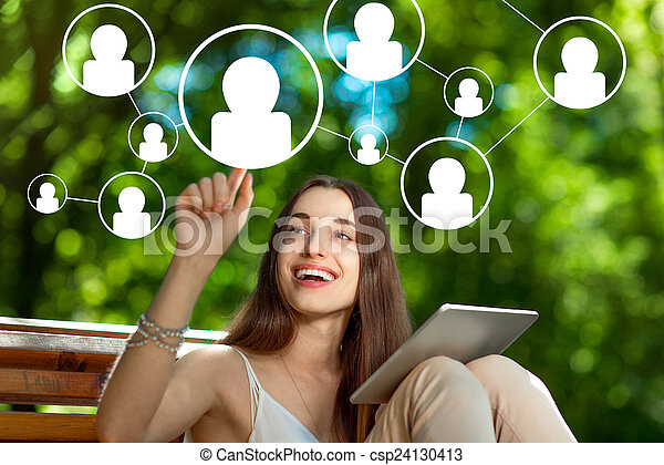 Young woman with digital tablet in the park - csp24130413