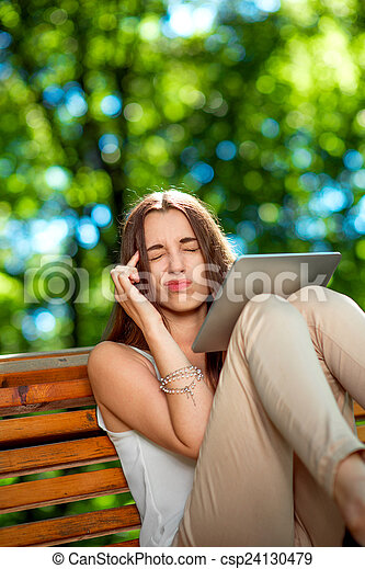 Young woman with digital tablet in the park - csp24130479