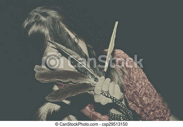 young woman with feathers in hand - csp29513150
