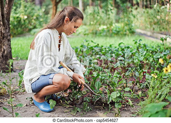 Young woman with hoe working in the garden bed - csp5454627