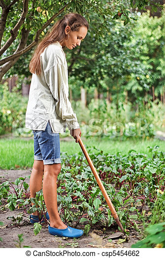 Young woman with hoe working in the garden bed - csp5454662
