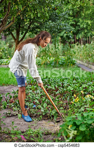 Young woman with hoe working in the garden bed - csp5454683