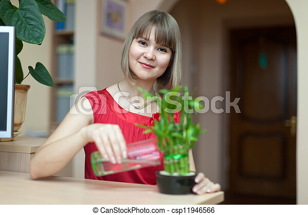 Young woman with lucky bamboo plant   - csp11946566