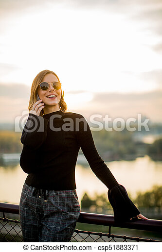 Young woman with mobile phone outdoor - csp51883371