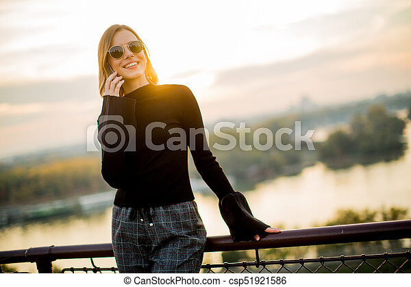 Young woman with mobile phone outdoor - csp51921586
