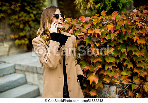 Young woman with mobile phone outdoor - csp51883348