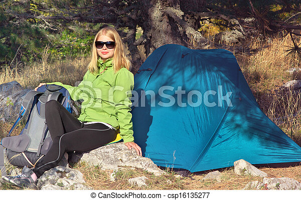 Young Woman with Smiling Face Hiker sitting with backpack and Tent Camping Outdoor on Grass with forest nature on background Travel and Healthy Lifestyle concept - csp16135277