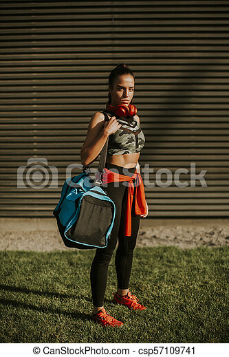 Young woman with sport bag outdoor - csp57109741