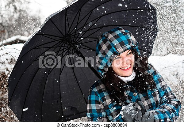 Young woman with umbrella in a blizzard - csp8800834