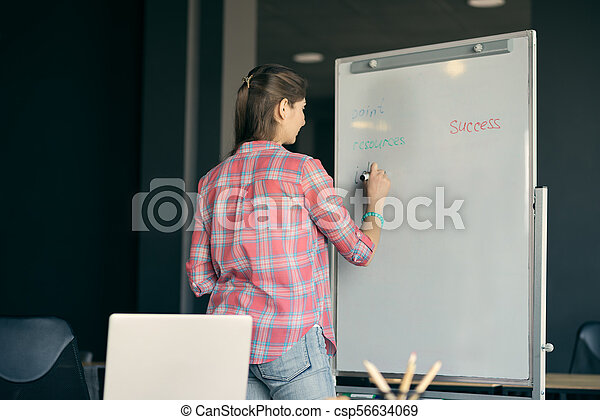 Young Woman Writes on White Board During Lecture or Project Presentation. Business or Education Concept. - csp56634069
