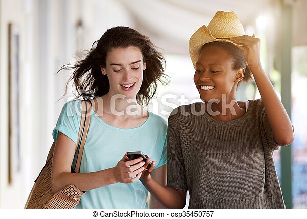 Young women walking together using cellphone - csp35450757