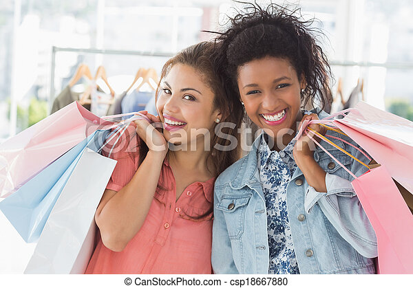Young women with shopping bags in clothes store - csp18667880