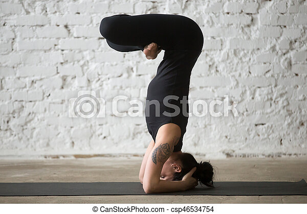 young yogi attractive woman in headstand pose white loft