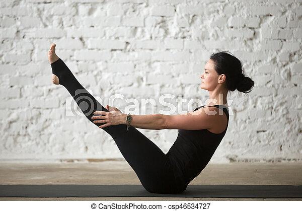 young yogi attractive woman in paripurna navasana pose