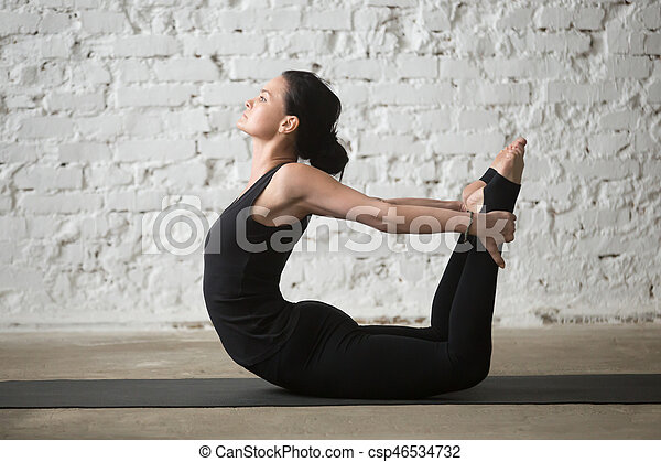 young yogi attractive woman in dhanurasana pose white
