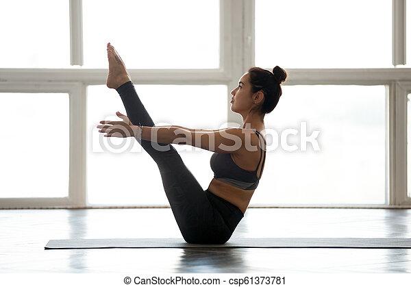 young yogi woman practicing yoga navasana boat pose