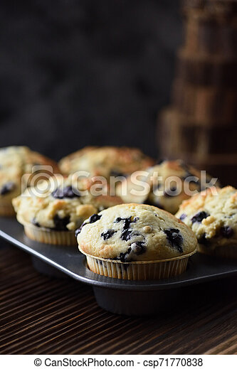 Yummy crumble top blueberry muffins in baking pan on black background with natural lighting copy space - csp71770838