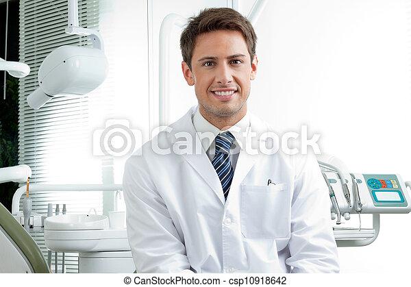 Ein glücklicher männlicher Zahnarzt in der Klinik - csp10918642