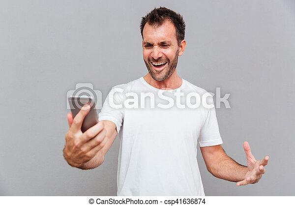 zangado, smartphone, casual, segurando, homem - csp41636874