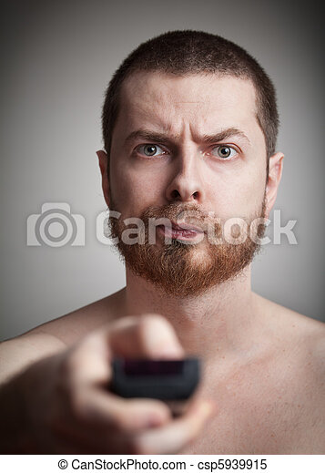Zapping - annoyed man with tv remote control - csp5939915
