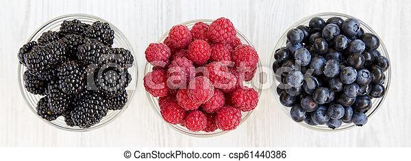 Tazones llenos con bayas: arándanos, moras, frambuesas. Comida saludable y dieta. Desde arriba, desde arriba, desde arriba. - csp61440386