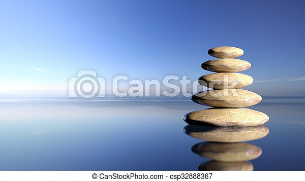 Zen stones stack from large to small in water with blue sky and peaceful landscape background. - csp32888367