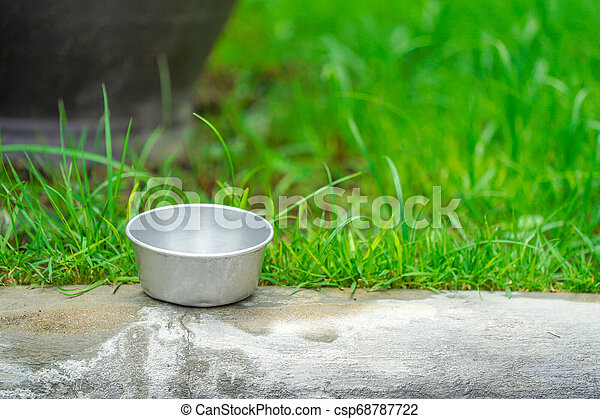 zinc cup on the foot-part with green garden background. - csp68787722